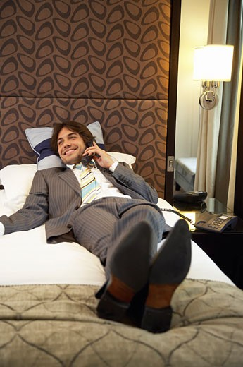 Businessman Using Telephone in Hotel Room    : Stock Photo
