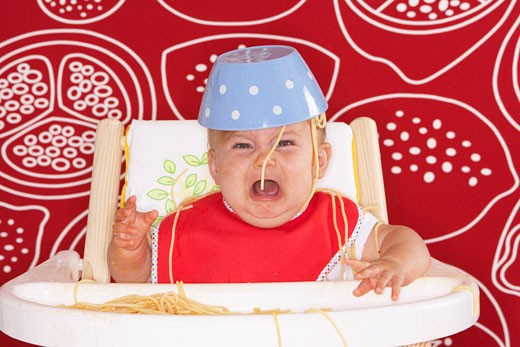 Baby in High Chair with Spaghetti Bowl on Head    : Stock Photo
