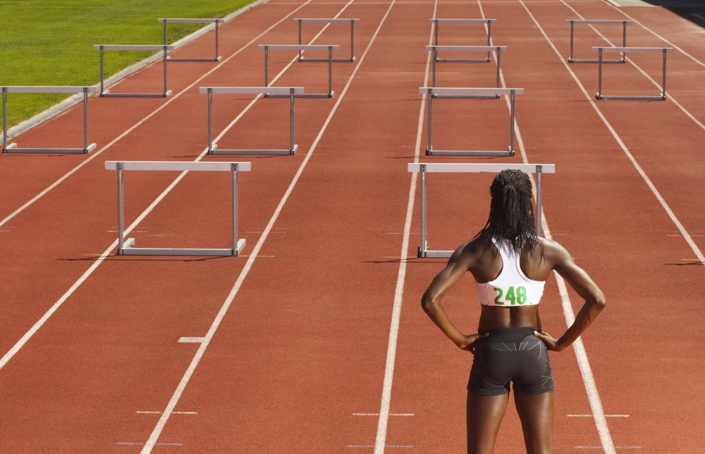 Back View of Woman Standing in Front of Hurdles on Track    : Stock Photo