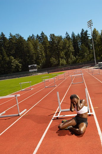 Stock Photo: 1828R-14708 Woman Sitting on Running Track after Stumbling