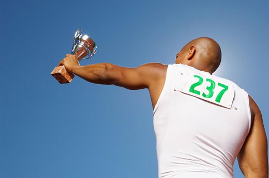 Stock Photo: 1828R-14747 Champion Athlete Holding Trophy
