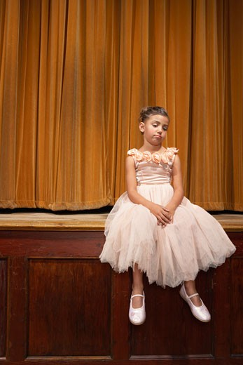 Stock Photo: 1828R-14953 Girl Sitting on Stage