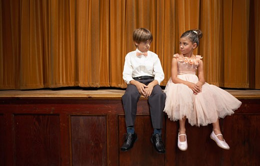 Stock Photo: 1828R-14955 Boy and Girl Sitting on Stage
