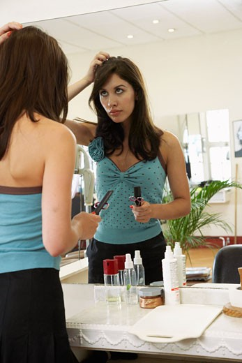Stock Photo: 1828R-15112 Hair Stylist Looking at Reflection in Mirror