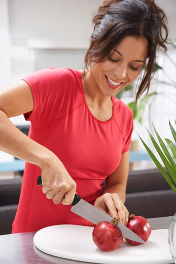 Stock Photo: 1828R-15158 Woman Cutting Pomegranate