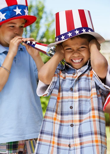 Stock Photo: 1828R-15774 Portrait of Boy Wearing Stars and Stripes Hat with Boy Blowing Noisemaker Horn