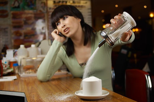 Stock Photo: 1828R-15839 Woman Distracted by Phone Call, Filling Cup with Sugar