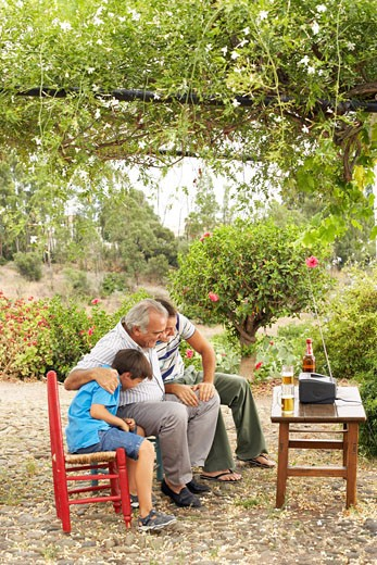Stock Photo: 1828R-16143 Grandfather, Father and Son Watching Television in Backyard