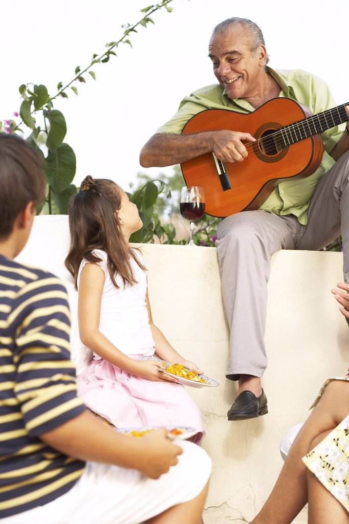 Stock Photo: 1828R-16174 Man Playing Guitar Outdoors with Children Listening