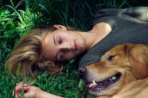Girl Lying down with Golden Retriever    : Stock Photo
