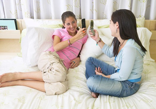 Stock Photo: 1828R-16242 Friends Using Cellular Phones on Bed