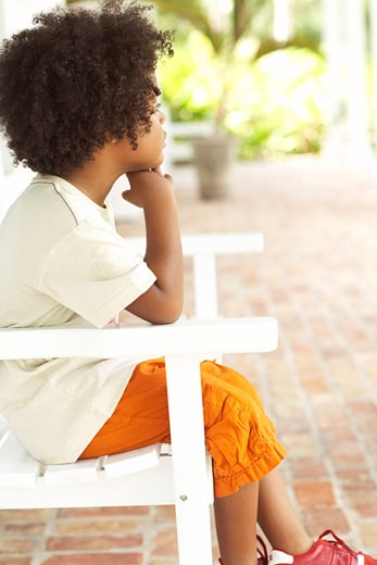 Stock Photo: 1828R-16495 Boy Sitting in Chair Outdoors
