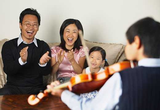 Stock Photo: 1828R-16718 Family Watching Boy Play Violin