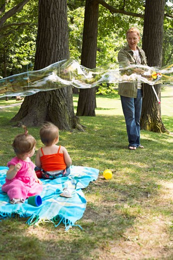 Father Blowing Bubbles while Babies Watch    : Stock Photo
