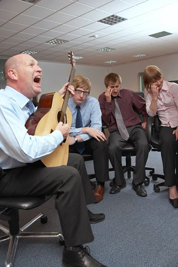 Stock Photo: 1828R-17258 Manager Playing Guitar for Employees