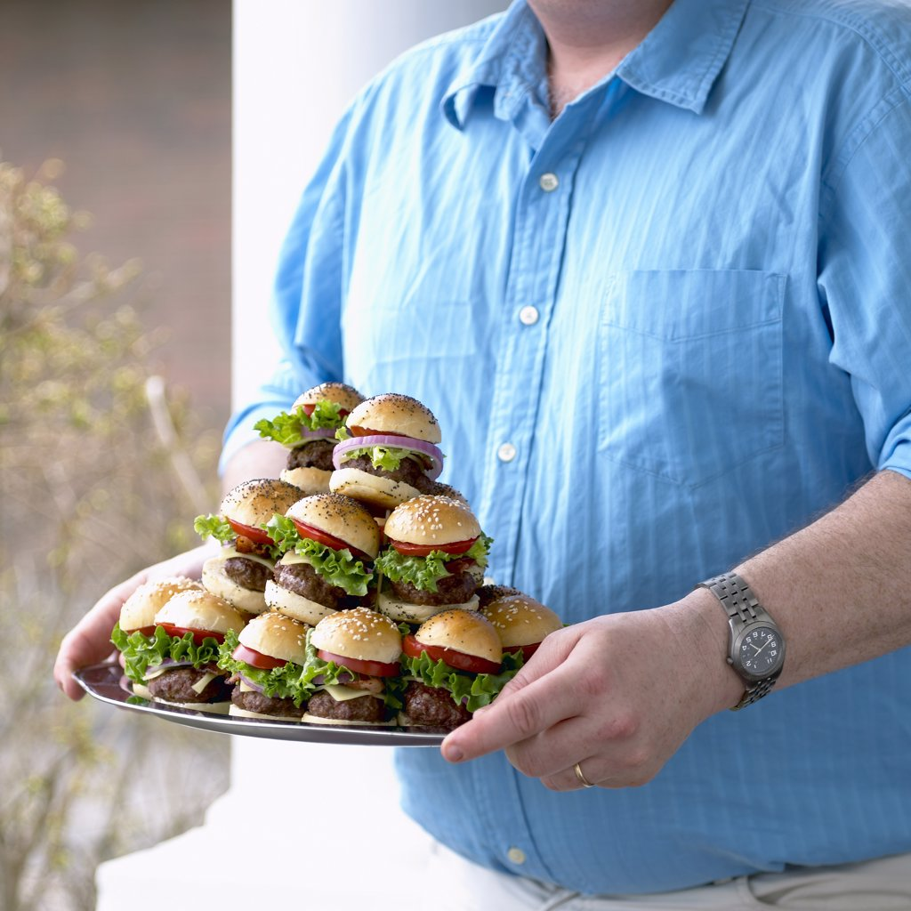 Man Carrying Plate of Small Hamburgers    : Stock Photo