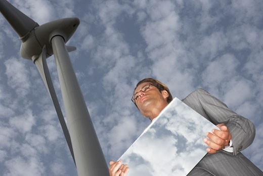 Stock Photo: 1828R-18099 Businessman with Mirror by Wind Turbine