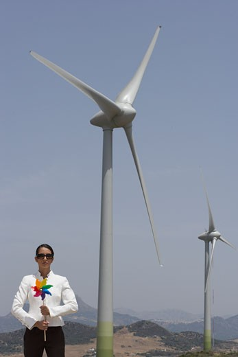 Businesswoman with Pinwheel by Wind Turbine    : Stock Photo