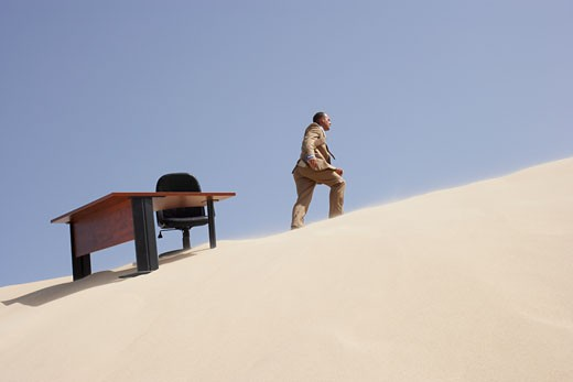 Stock Photo: 1828R-18147 Businessman Walking away from Office on Sand Dune