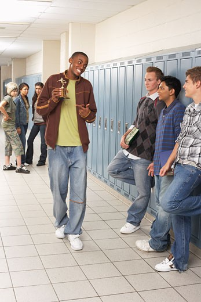 Boy Showing off Trophy in High School Hallway    : Stock Photo