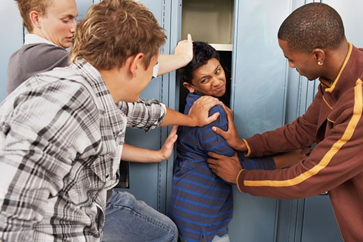 Stock Photo: 1828R-18852 Group of Teens Stuffing Boy in Locker