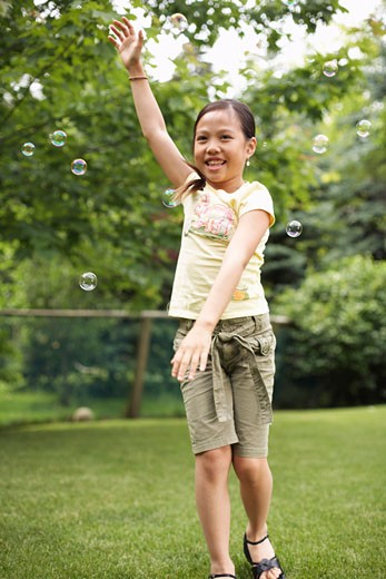 Stock Photo: 1828R-19427 Girl Playing With Bubbles
