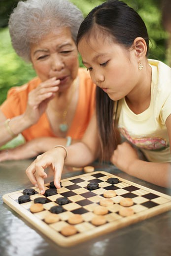 Stock Photo: 1828R-19441 Grandmother Helping Granddaughter Play Checkers