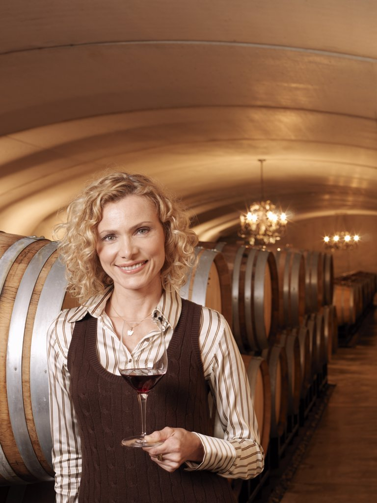 Woman Standing in Wine Cellar    : Stock Photo