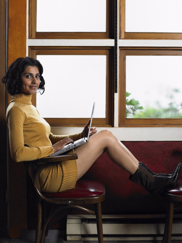 Stock Photo: 1828R-19823 Woman by Window with Laptop Computer