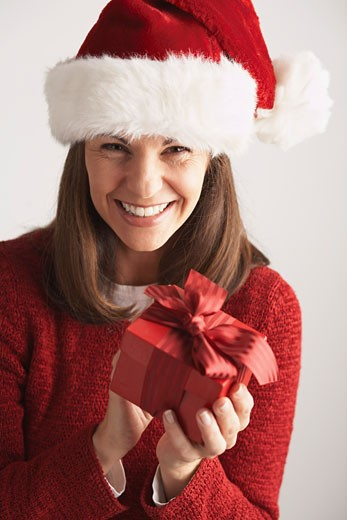 Stock Photo: 1828R-20265 Woman in Santa Hat Holding Gift