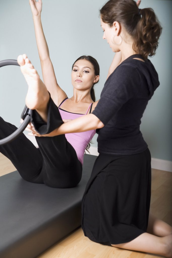 Stock Photo: 1828R-20683 Woman Exercising with Personal Trainer