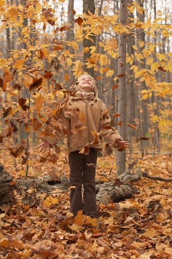 Stock Photo: 1828R-20783 Girl Standing in Autumn Leaves