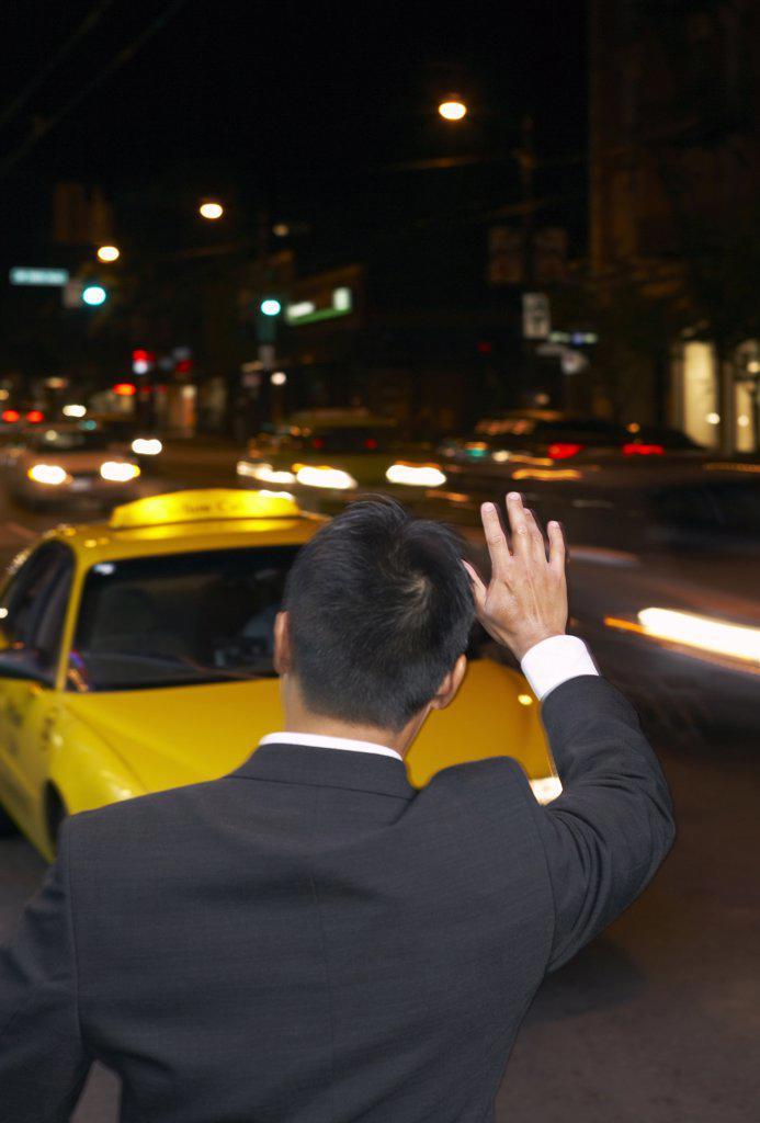 Stock Photo: 1828R-20864 Man Hailing Cab at Night