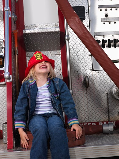 Stock Photo: 1828R-21230 Girl on Back of Fire Truck