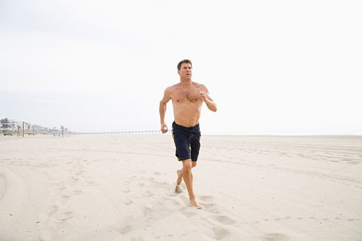 Stock Photo: 1828R-21266 Man Running on Beach