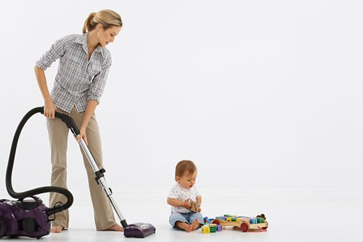 Stock Photo: 1828R-21512 Woman Vacuuming, Baby Playing with Toys