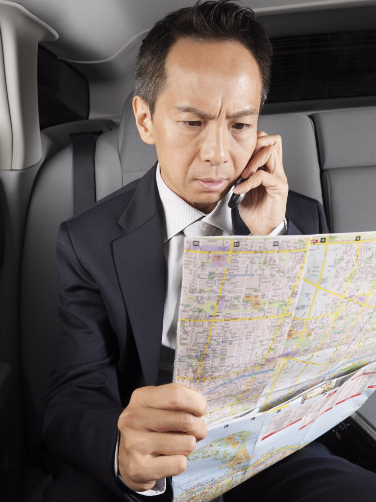 Stock Photo: 1828R-21802 Businessman Looking at Map in Car