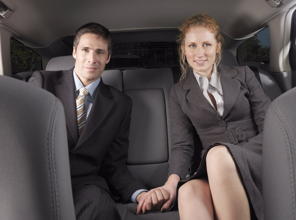 Stock Photo: 1828R-21872 Man and Woman Holding Hands in Back of Car