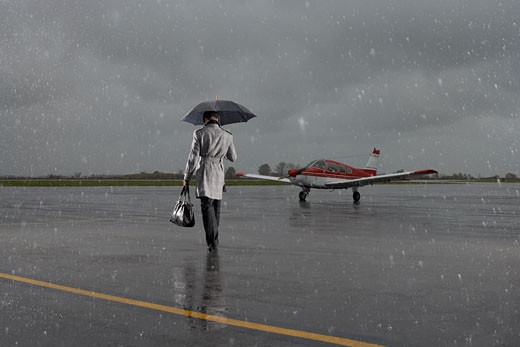 Stock Photo: 1828R-21899 Backview of Businessman Walking on Tarmac in Rainy Weather