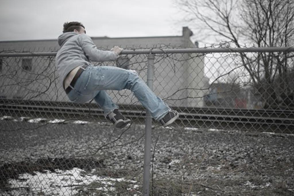 Man Climbing over Fence    : Stock Photo
