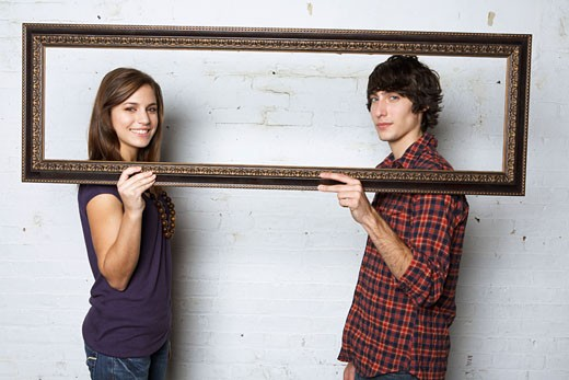Stock Photo: 1828R-22355 Young Couple Holding Picture Frame