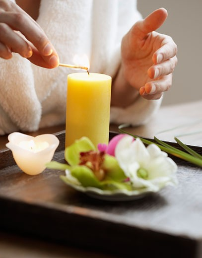 Stock Photo: 1828R-23953 Woman Lighting Candle