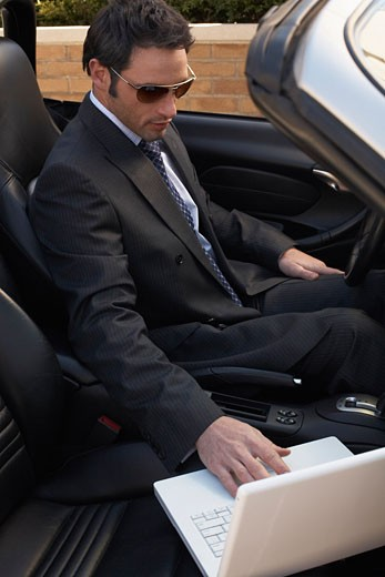 Stock Photo: 1828R-25755 Businessman in Car with Laptop Computer
