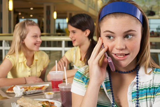 Stock Photo: 1828R-25799 Teenager on Cell Phone with Friends in Background