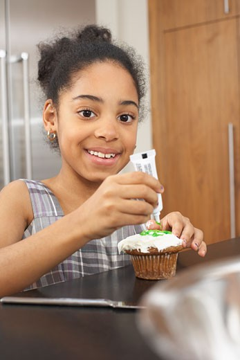 Stock Photo: 1828R-26412 Girl Putting Icing on Cupcake
