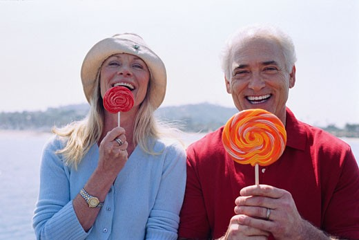 Stock Photo: 1828R-26610 Portrait of Couple Eating Lollipops