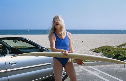 Stock Photo: 1828R-26617 Woman Holding Surf Board at Beach, Standing Beside Car