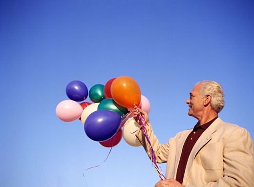 Man Holding Bunch of Balloons    : Stock Photo