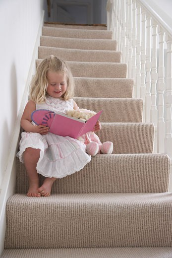 Stock Photo: 1828R-27092 Girl Reading Book on Staircase