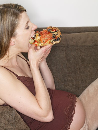 Stock Photo: 1828R-27232 Pregnant Woman Eating Pizza